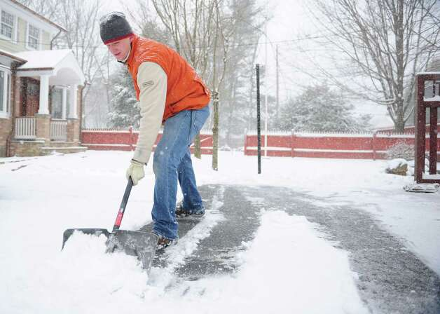 Robert Kanoza shovels his driveway for a third time as snow continues to fall in Shelton, Conn. Friday, Feb. 8, 2013. Photo: Autumn Driscoll