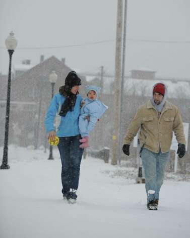Jamie and Sasha Bratt take a snowy walk to Veteran's Memorial Park in Shelton, Conn. with their 15-month-old daughter Mina Friday, Feb. 8, 2013. Photo: Autumn Driscoll