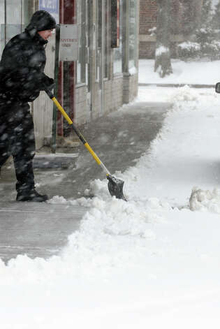 Brian Porter, a worker with B&J Enterprises in Milford, shovels snow in front of a section of businesses along West River Street as a major snow storm hits the region in Milford Conn. on Friday February 8, 2013. Photo: Christian Abraham / Connecticut Post