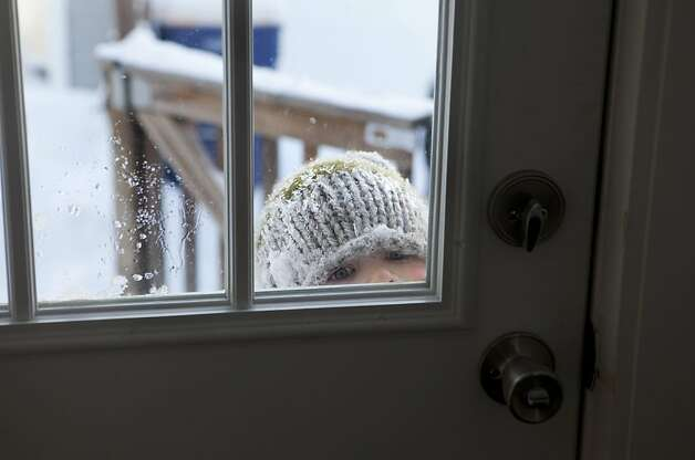 Mom, my boot fell off: Five-year-old Lucas Struck-VanderHaak peers into his home in Grand Rapids, Mich., while asking his mom to adjust his snow boot. Photo: Emily Zoladz, Associated Press