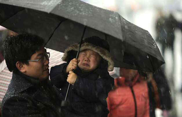 Late again! Oh, noooo! Father and son wait for a train at the main railroad station in Shanghai. Photo: Eugene Hoshiko, Associated Press