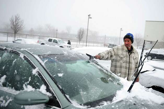 Leon Smith cleans off his car as he leaves work at Inline Plastics Corp. in Shelton, Conn. Friday, Feb. 8, 2013.  Employees went home after half a day due to the blizzard. Photo: Autumn Driscoll