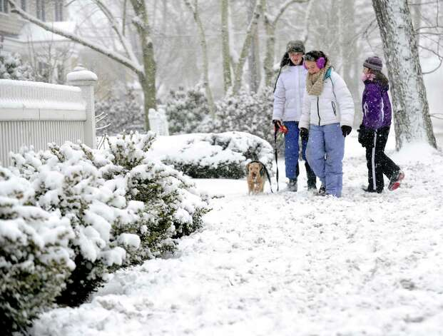 Delia Murphy and her sister, Lulu Murphy walk their dog, Gibson with the help of their friend Caitlin Cavanaugh along the Old Post Rd. in Fairfield, Conn. on Friday, Feb. 8, 2013. Several inches of slick, heavy snow have already fallen across southwestern Connecticut and it will steadily increase overnight with totals of over a foot possible. Photo: Cathy Zuraw / Connecticut Post