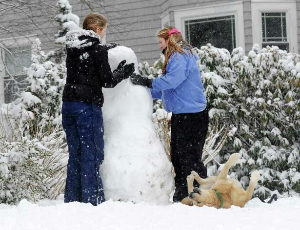 Caroline Wolstenholme and Ashton Guifoile buld a snowman on Rowland Rd. in Fairfield, Conn. on Friday, Feb. 8, 2013. Honey, the yellow lab, prefers to roll around in the cold wet stuff.  According to the National Weather Service, southwestern Connecticut could get 10 to 14 inches before the storm ends. Photo: Cathy Zuraw / Connecticut Post