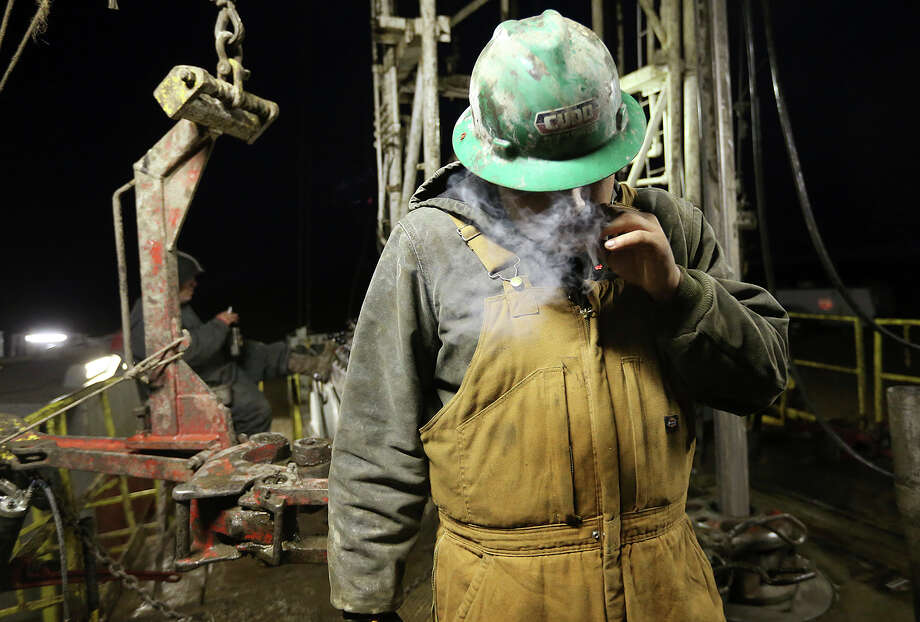 Before the start of the day, floorhand Miguel Ortiz, 21, of Alamo, Texas smokes a cigarette at a drilling rig in Frio County, Monday, Jan. 21, 2013. Photo: Jerry Lara, San Antonio Express-News / © 2013 San Antonio Express-News
