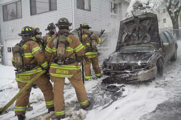 Stamford Fire and Rescue Department firefighters douse a care fire at 60 Anderson St. in Stamford, Conn. on Friday, Feb. 8, 2013. Photo: Chris Preovolos / Stamford Advocate