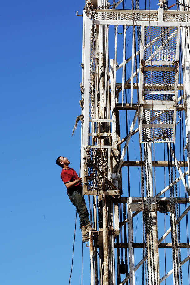 "Anatolio Salinas climbs up the rig as it is erected and prepared for drilling at a site in Frio County, Thursday, Jan. 17, 2013. The ""total depth"" for the drilling was at 4,000 feet with the main area of interest was a formation called the San Miguel Sandstone. Photo: Jerry Lara, San Antonio Express-News / © 2013 San Antonio Express-News"