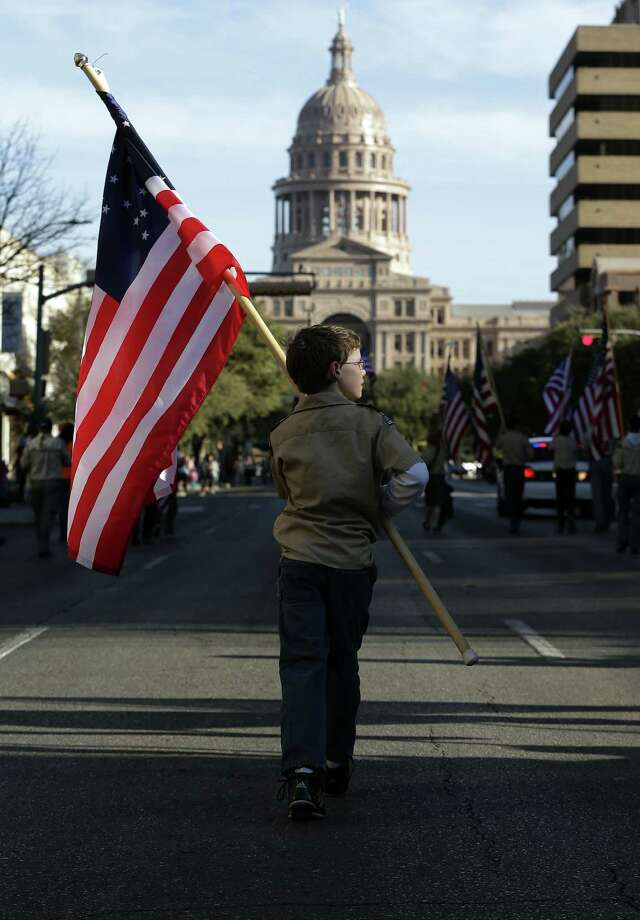 Boy Scouts carry U.S. flags toward the Texas Capitol during the annual Boy Scouts Parade and Report to State  in Austin. A reader is dissapointed that the Boy Scouts ban on gays may result in funding cuts.