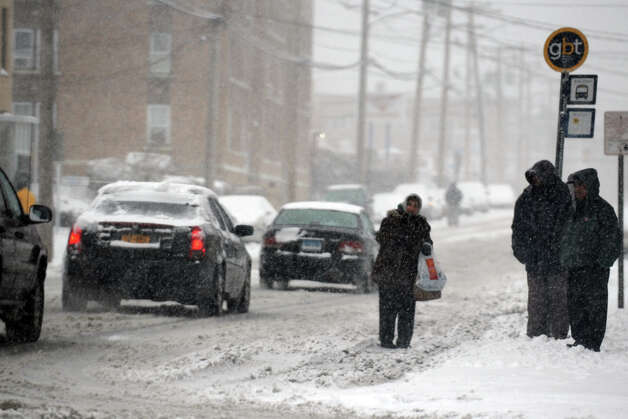 Pedestrians wait in the snow for a bus along Main Street, in Bridgeport, Conn., Feb. 8th, 2013. Photo: Ned Gerard / Connecticut Post