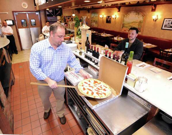 At left, Mark Mazzotta, owner of Pomodoro Pizzeria & Trattoria of Riverside puts a pizza in a box for customer David Balog, right, of Danbury, during the snowstorm that hit Greenwich, Conn., Friday, Feb. 8, 2013. Mazzotta said the bad weather was slowing down business but was staying open for his loyal customers. Photo: Bob Luckey / Greenwich Time