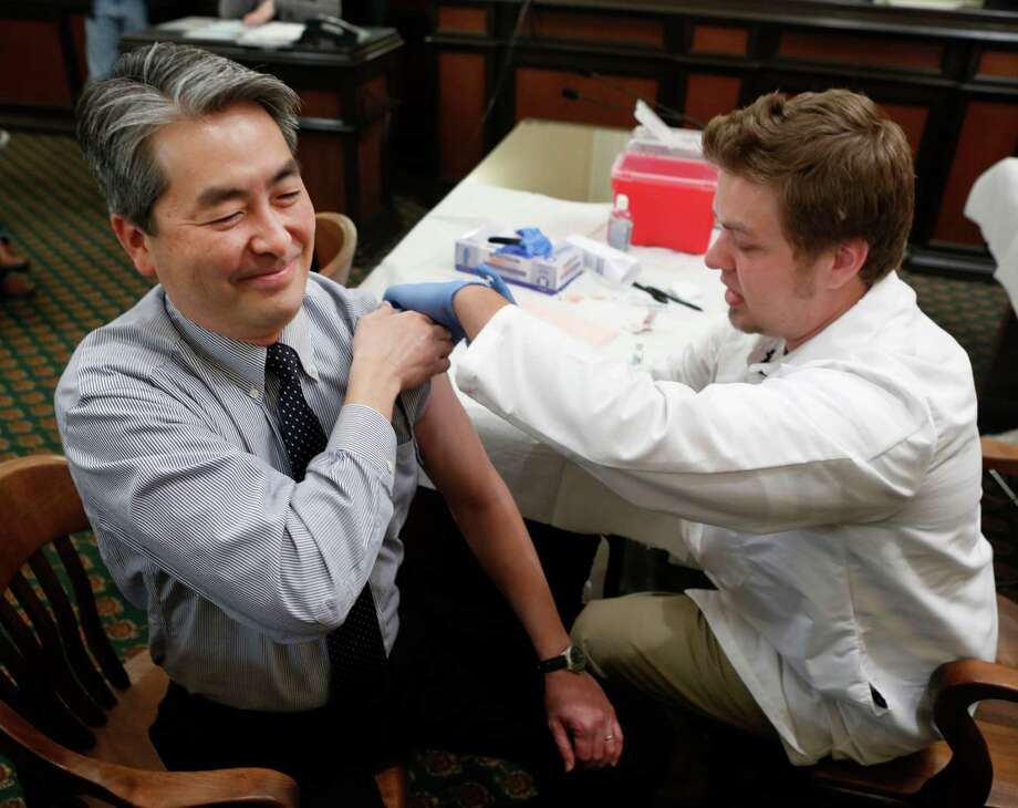 FILE - In this Monday, Jan. 28 , 2013 file photo, Assemblyman Al Muratsuchi, D-Torrance, reacts as he receives a flu shot from Tyler Poncy, a licensed vocational nurse during a free flu vaccine clinic at the Capitol in Sacramento, Calif. Health officials say the worst of the flu season appears to be over. The number of states reporting intense or widespread flu dropped again in late January 2013. The Centers for Disease Control and Prevention released the latest flu numbers on Friday, Feb. 8, 2013. (AP Photo/Rich Pedroncelli) Photo: Rich Pedroncelli, STF / AP