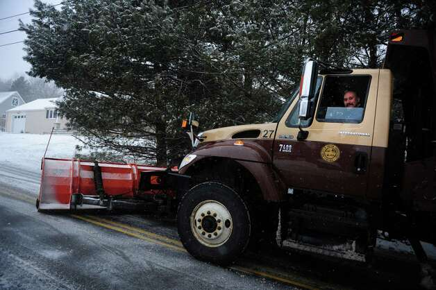 A plow at work as snow falls in Shelton, Conn. Friday, Feb. 8, 2013. Photo: Autumn Driscoll