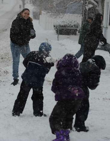 Crystal Murphy, left, is the target during a snowball fight Friday, Feb. 8, 2013 in Derby, Conn. Photo: Autumn Driscoll