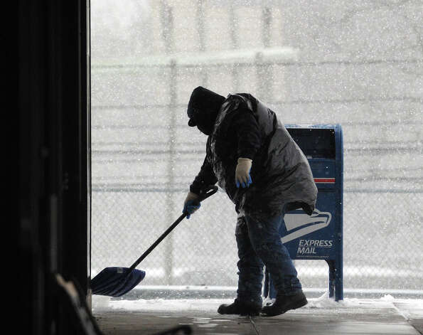 Juan Martinez shovels snow in the Riverside Commons Shopping Plaza during the snowstorm that hit Greenwich, Conn., Friday, Feb. 8, 2013. Photo: Bob Luckey / Greenwich Time