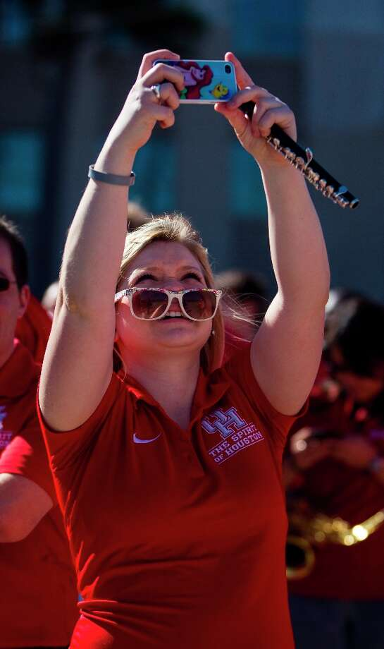 Sophomore Delaney Marth a member of the UH marching band, takes a photo during the groundbreaking ceremony. Photo: Karen Warren / © 2013 Houston Chronicle