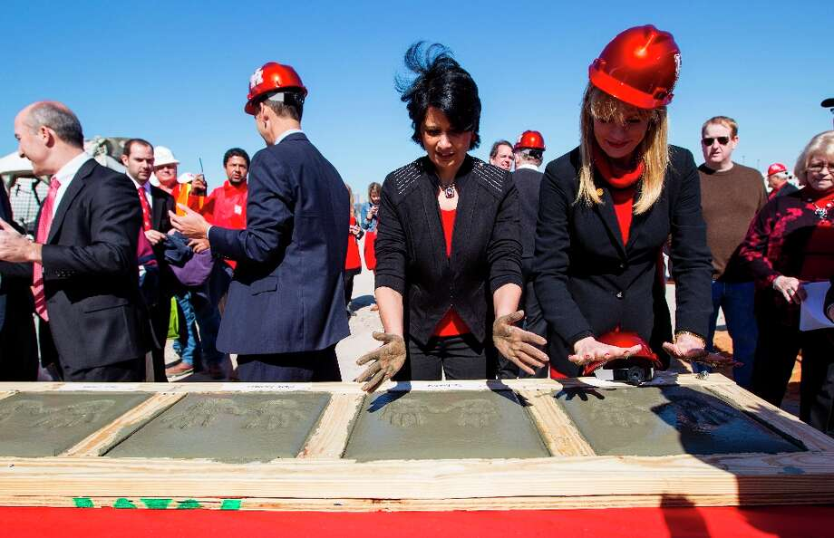 University of Houston president Renu Khator, left, and Nelda Luce Blair, right, Chairman of the UH System Board of Regents, lift their hands out of the cement blocks during the groundbreaking ceremony. Photo: Karen Warren / © 2013 Houston Chronicle