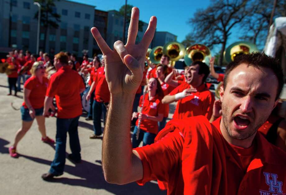 Joe Eck, graduate assistant in the band department, flashes the cougar paw as the UH marching band plays during the groundbreaking ceremony. Photo: Karen Warren / © 2013 Houston Chronicle