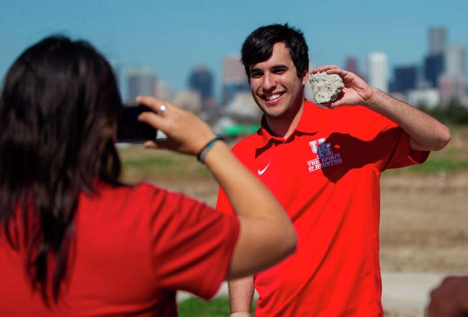 UH band member Danny Rojas, 21, gets his photo taken by fellow band member Francesca Berntsen, 23, holding a piece of the old Robertson stadium after the groundbreaking ceremony. Photo: Karen Warren / © 2013 Houston Chronicle