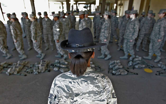 Staff Sgt. Katrenvious Swift (foreground), a military training instructor, observes drills from a flight of Air Force basic trainees at Joint Base San Antonio - Lackland on Friday, Feb. 8, 2013. Swift is one of 53 female instructors in the Air Force. As part of the recommendations from an investigation stemming from  numerous cases of sexual assault, new procedures and implementations have been started or put into place at Lackland. One of the new policies include having one female trainer on each team like Swift. Photo: Kin Man Hui, San Antonio Express-News / © 2012 San Antonio Express-News