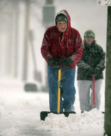 Jim and Holly Sheehy shovel the sidewalk in front of their home in Ansonia, Conn. Friday, Feb. 8, 2013. Photo: Autumn Driscoll