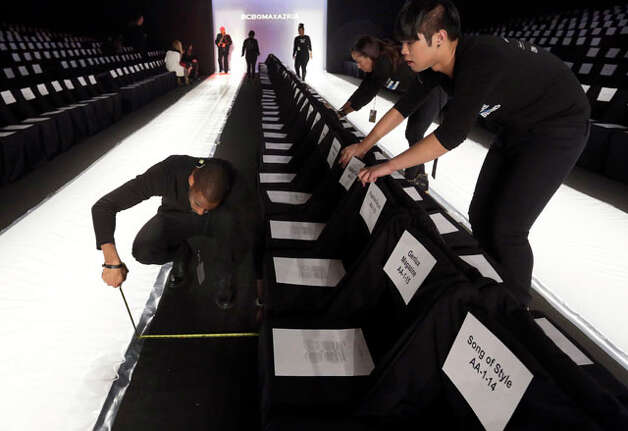 Workers use a tape measure to align seating on the runway before the BCBG Max Azria Fall 2013 collection is modeled during Fashion Week in New York,  Thursday, Feb. 7, 2013. (AP Photo/Richard Drew) Photo: Richard Drew, Wire Photos / AP
