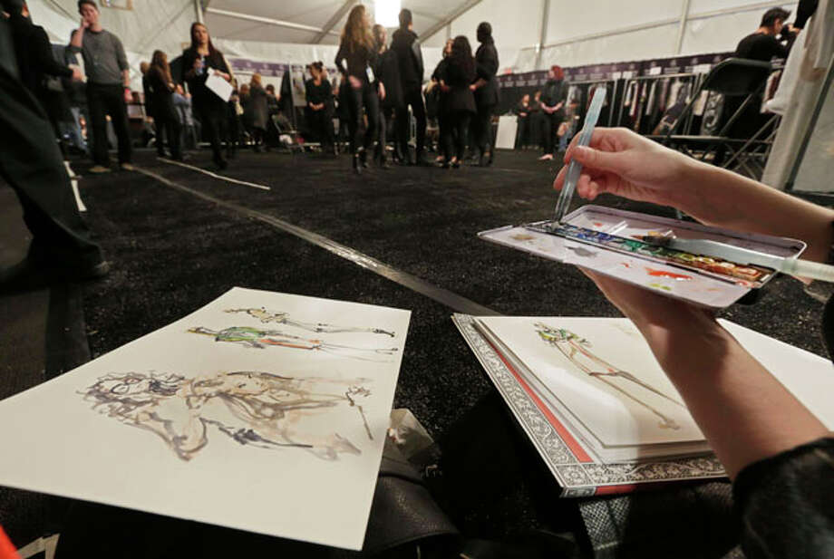 Fashion illustrator Danielle Meder paints with watercolors backstage before the BCBG Max Azria Fall 2013 collection is modeled, during Fashion Week in New York,  Thursday, Feb. 7, 2013. (AP Photo/Richard Drew) Photo: Richard Drew, Wire Photos / AP