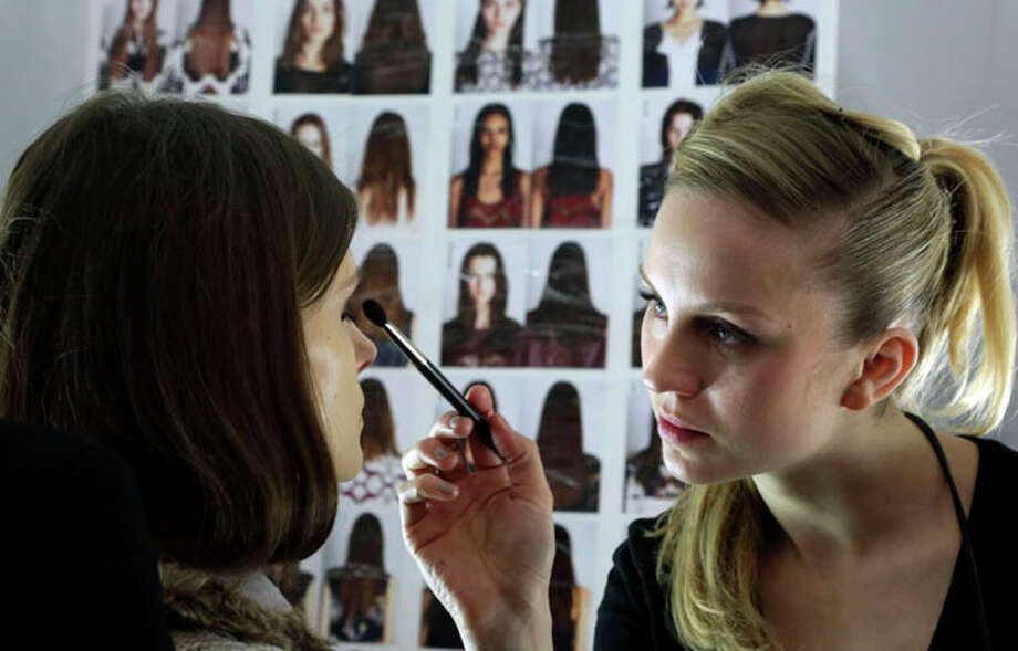 A model has make-up applied backstage before the BCBG Max Azria Fall 2013 collection is modeled during Fashion Week in New York,  Thursday, Feb. 7, 2013. (AP Photo/Richard Drew) Photo: Richard Drew, Wire Photos / AP