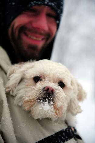 Fred Smith keeps his dog Bo warm in his jacket during a snowy walk in Ansonia, Conn. Friday, Feb. 8, 2013. Photo: Autumn Driscoll