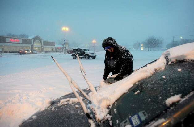 Alex Alcaraz cleans off his car after getting off work at the ShopRite in Fairfield, Conn. on Friday, Feb. 8, 2013. The snow started around 7 a.m. across southwestern Connecticut and steadily increased throughout the day. The storm is expected to continue overnight with high winds and the potential for over a foot of snowfall. Photo: Cathy Zuraw / Connecticut Post
