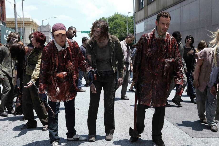 With their group stuck in the department store, Rick and Glenn cover themselves in walker blood and guts to mask their scent as they head towards a truck. Photo: Scott Garfield/Courtesy Of AMC