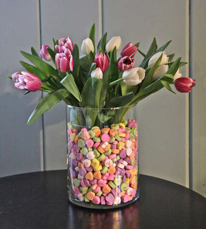 Tulips are nestled in a vase filled with candy hearts.