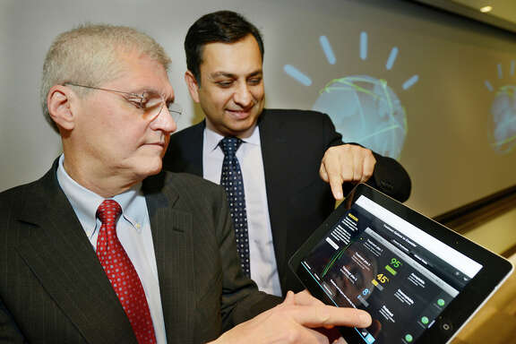 "In this photo provided by International Business Machines, (IBM) Mark Kris, MD, Chief of Thoracic Oncology, Memorial Sloan-Kettering Cancer Center, left, and Manoj Saxena, IBM General Manager, Watson Solutions, demonstrate a tablet which will be used by both doctors and health Insurance to access medical applications on IBM's ""Watson"" computer system, Friday, Feb. 8, 2013 in Armonk, N.Y. IBM Corp., the health insurer WellPoint Inc. and Memorial Sloan-Kettering Cancer Center announced two Watson-based applications on Friday, one to help diagnose and treat lung cancer and one to help manage health insurance decisions and claims. (AP Photo/IBM, Jon Simon)"