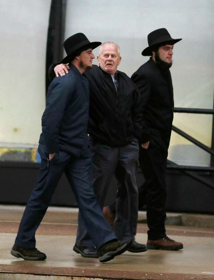 Amish men walk to the U.S. Federal Courthouse Friday, Feb. 8, 2013, in Cleveland.  A judge will sentence 16 Amish for hate-crimes convictions in beard- and hair-cutting attacks on fellow Amish Friday, a case that highlighted issues of dissent and rogue discipline amid an idyllic rural lifestyle of horse buggies and wood stoves. (AP Photo/Tony Dejak) Photo: Tony Dejak