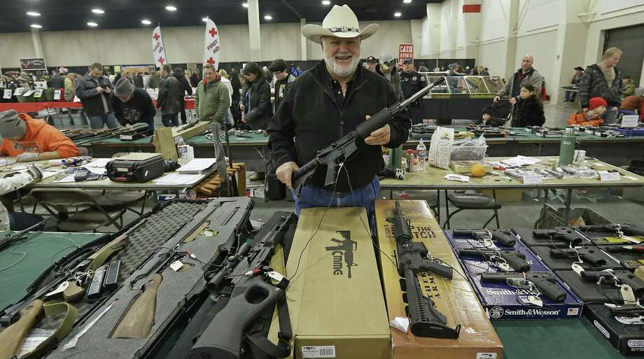 "FILE - In this Jan. 6, 2013 file photo, Ken Haiterman, of Pioneer Market, holds a CMMG 5.56mm AR 15 during the 2013 Rocky Mountain Gun Show in Sandy, Utah. A bipartisan quartet of senators, including two National Rifle Association members and two with ""F"" ratings from the potent firearms lobby, are quietly trying to reach compromise on expanding the requirement for gun-sale background checks. (AP Photo/Rick Bowmer, File) Photo: Rick Bowmer"