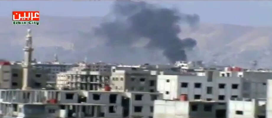 This image taken from video obtained from Ugarit News on Friday, Feb. 8, 2013, which has been authenticated based on its contents and other AP reporting, show smoke rising from fighting near a main highway in Damascus, Syria. Rebels pushed forward in their battle with the Syrian army in northeastern Damascus on Friday, shutting down a main highway with a row of burning tires, activists said. A number of rebel brigades launched a campaign Wednesday to attack regime checkpoints along the highway and have been clashing in the area since. The government has responded by shelling number of rebel areas nearby. (AP Photo/Ugarit News via AP video) Photo: Anonymous