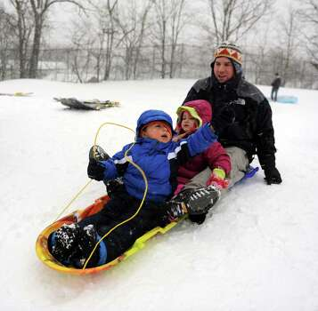 From left, Mateo Rojas, 3, Grace Agneto, 3, and Nick Agneto sled at E. Gaynor Brennan Municipal Golf Course during the blizzard Friday, February 8, 2013. Photo: Lindsay Perry / Stamford Advocate