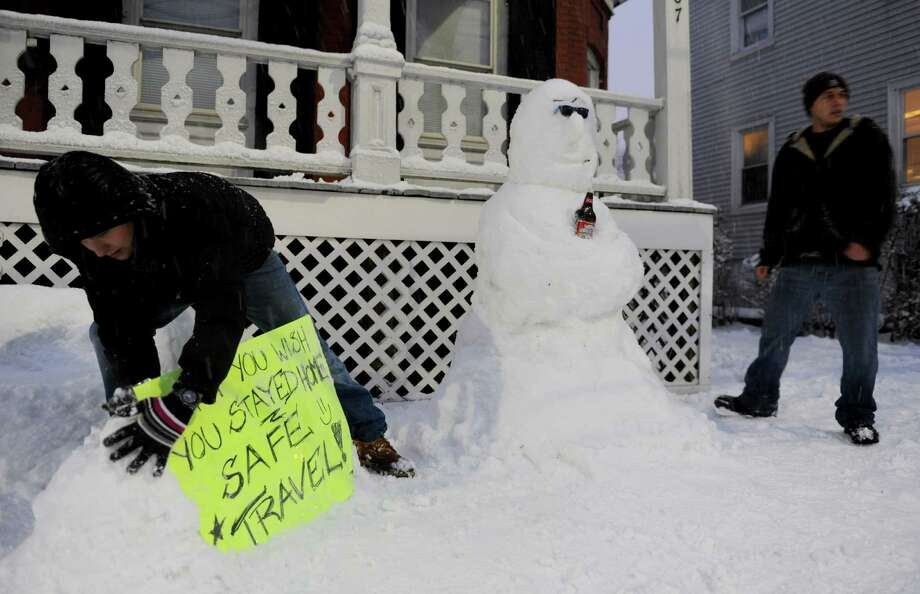 UCONN Stamford students Aleksey Fadeichev, left, and Nick Moore, right, create a snow sculpture during the blizzard Friday, February 8, 2013. Photo: Lindsay Perry / Stamford Advocate