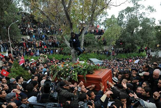 Tunisians carry the coffin of assassinated opposition leader Chokri Belaid ahead of his burial at El-Jellaz cemetery in a suburb of Tunis on February 8, 2013. Tunisian police fired tear gas and clashed with protesters as tens of thousands joined the funeral of Belaid whose murder plunged the country into new post-revolt turmoil.  Photo: Fethi Belaid, AFP/Getty Images