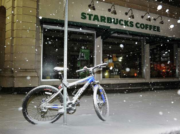 A bike covered with snow chained to a sign in front of Starbucks on Greenwich Avenue during the snowstorm that hit Greenwich, Conn., Friday, Feb. 8, 2013. Photo: Bob Luckey / Greenwich Time
