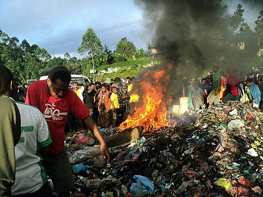 Bystanders watch as a woman accused of witchcraft is burned alive in Papua New Guinea. The young mother was stripped, tortured, bound, doused in gasoline and burned on a pile of trash. Photo: Associated Press