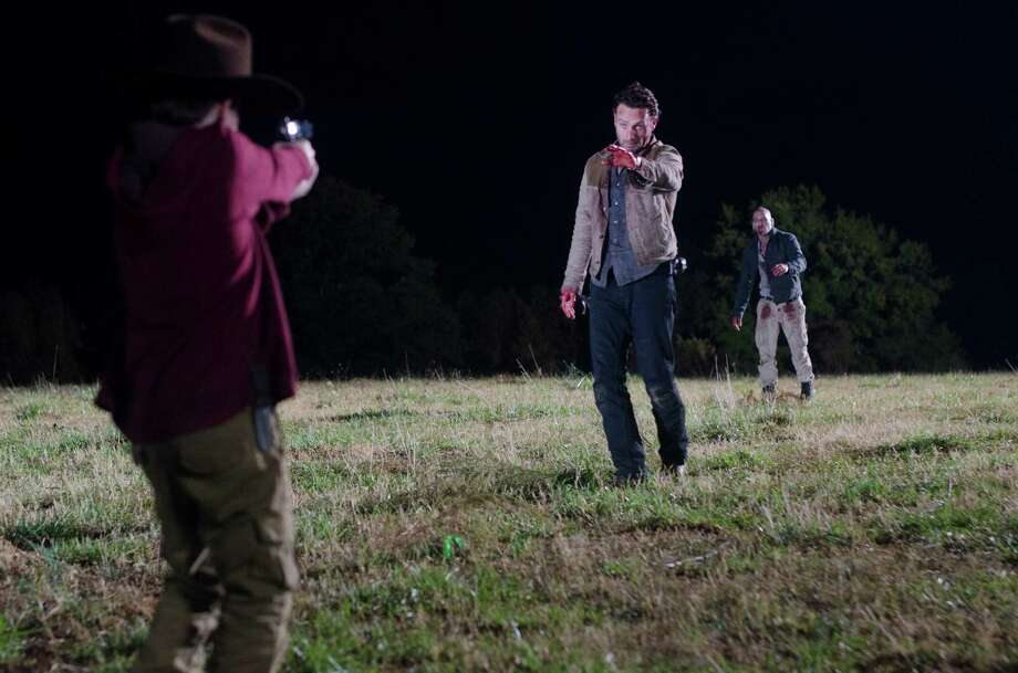 Carl saves his dad's life as Shane's reanimated corpse shambles behind him. Despite not being bitten, Shane exhibit walker attributes. Photo: Gene Page/Courtesy Of AMC
