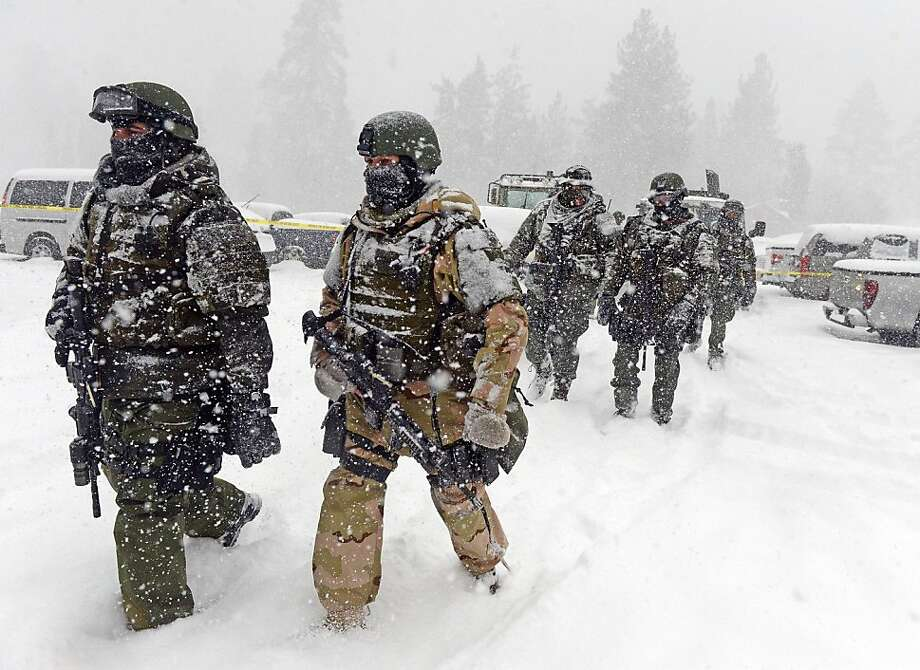 A San Bernardino County Sheriff SWAT team returns to the command post at Bear Mountain near Big Bear Lake, Calif. after searching for Christopher Jordan Dorner on Friday, Feb. 8, 2013. Search conditions have been hampered by a heavy winter storm in the area. Dorner, a former Los Angeles police officer, is accused of carrying out a killing spree because he felt he was unfairly fired from his job. (AP Photo/Pool, The Inland Valley Daily Bulletin, Will Lester) Photo: Will Lester, Associated Press