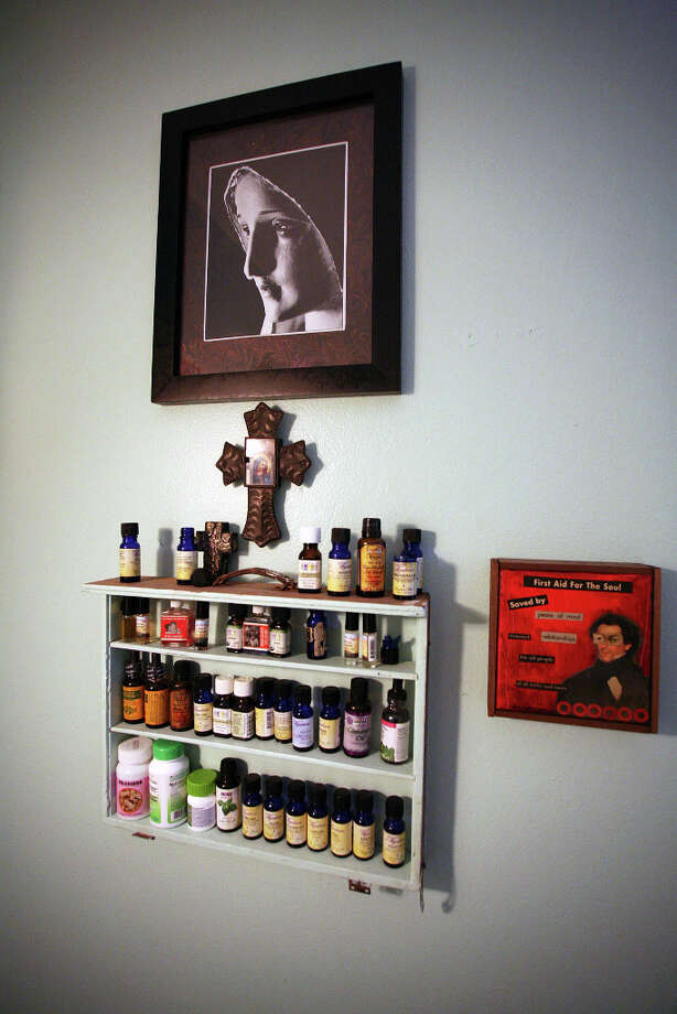 Art surrounds a repurposed drawer that Laurel Gibson mounted on the wall as a shelf to hold oils in her upstairs bathroom. Photo: Danny Warner, For The Express-News