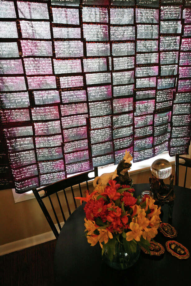 Laurel gibson used a wax pen to write the Song of Songs of Solomon from the Bible on fabric pieces that she stitched together to make a curtain in the breakfast nook. Photo: Danny Warner, For The Express-News