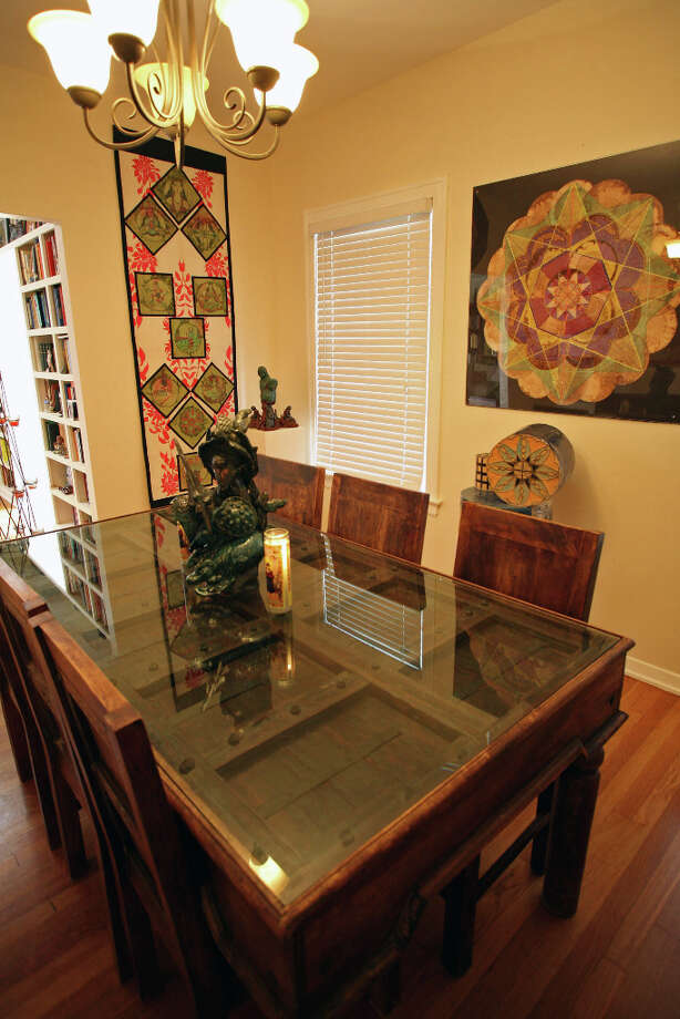 Laurel GibsonÕs ceramics and coffee filter art decorate the dining room. The table is made from an Indian door that's at least 200 years old. Photo: Danny Warner, For The Express-News