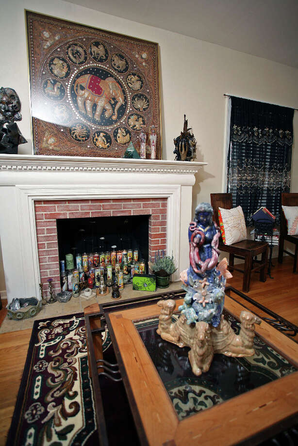 Laurel Gibson made the ceramics on the coffee table and mantel in her living room. The framed Indian embroidery above the mantel is a Goodwill find. Photo: Danny Warner, For The Express-News