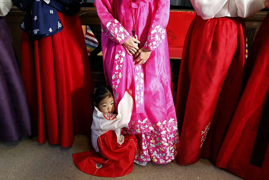 Three-year-old Zoe Chung clings to her mother, 2nd grade teacher Lissa Kim, during a celebration for