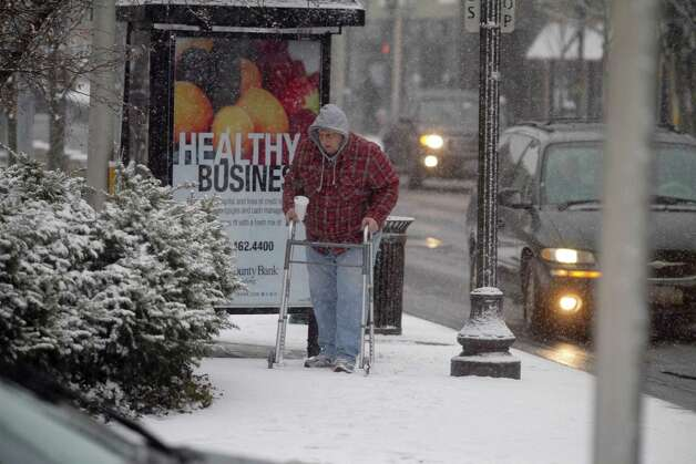 A man walks down Bedford Street in Stamford, Conn. during a snow storm on Friday, Feb. 8. 2013. Photo: Chris Preovolos / 2011