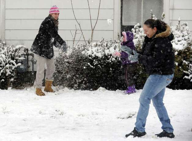 Jennifer Bacsik throws a snowball as friend Crystal Murphy braces for the hit during a snowball fight Friday, Feb. 8, 2013 in Derby, Conn. Photo: Autumn Driscoll