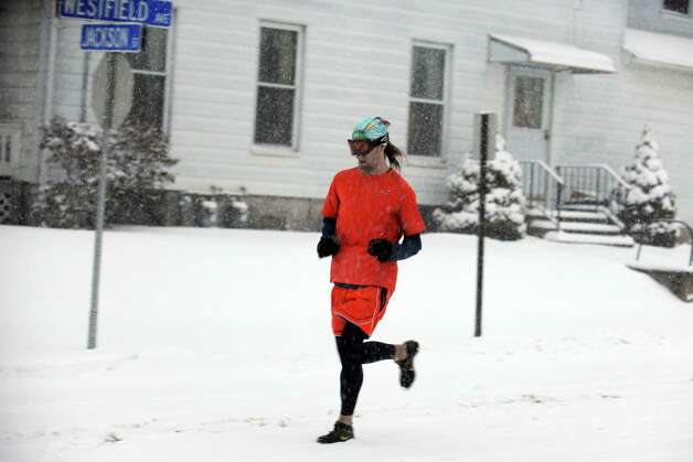 A man runs down Westfield Avenue in Ansonia, Conn. as snow falls Friday, Feb. 8, 2013. Photo: Autumn Driscoll